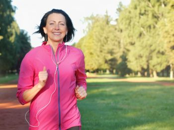 Portrait of elderly woman running with headphones in the park for laser treatments Dr. Irwin answers on SkinTour