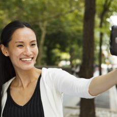A young happy woman taking a selfie with her smartphone. For beginner's guide to your first filler treatment Dr. Irwin answers on Skintour